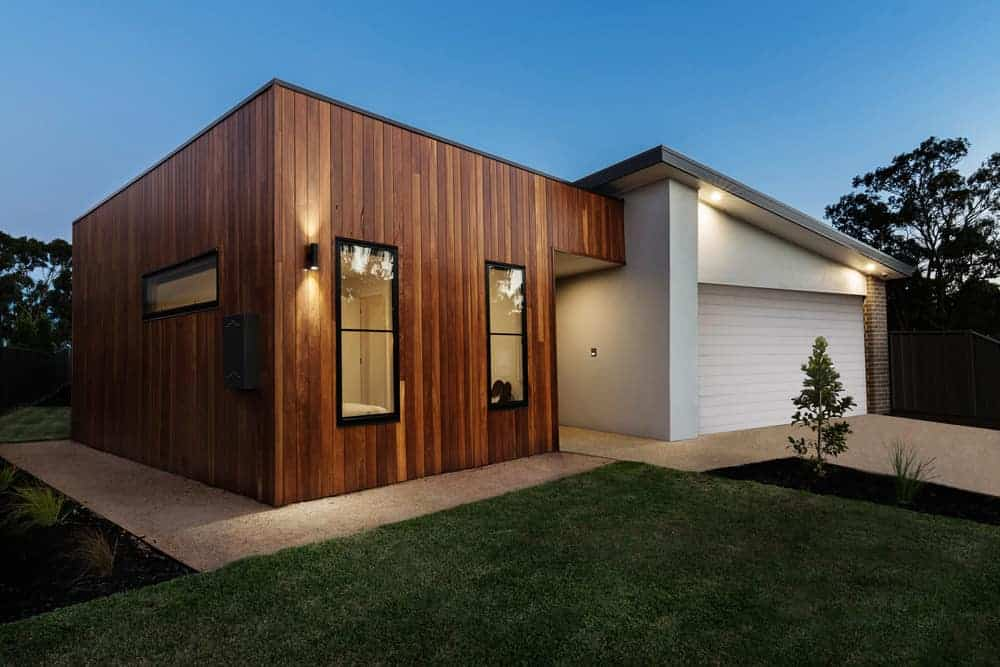Small contemporary home with vertical wood board exterior on the main part of the home which is contrasted with smooth stucco like exterior used on the garage half of th ehome.