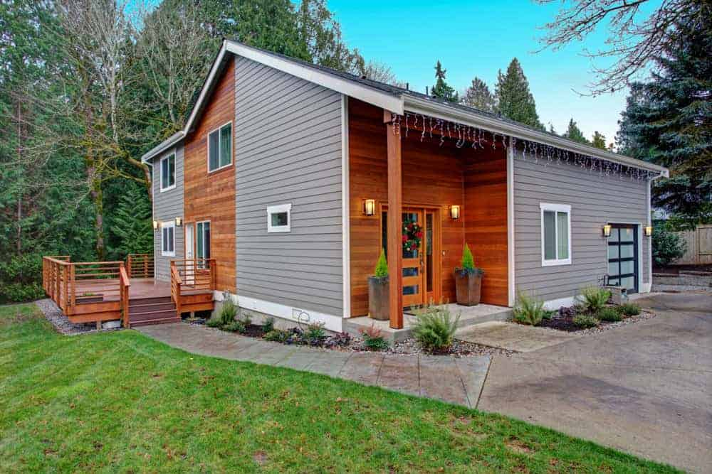 Wood board and vinyl siding combination make up this interesting home exterior. I really like this. It looks like a modern home, but it's not. The very different exteriors create an interesting effect that works well.