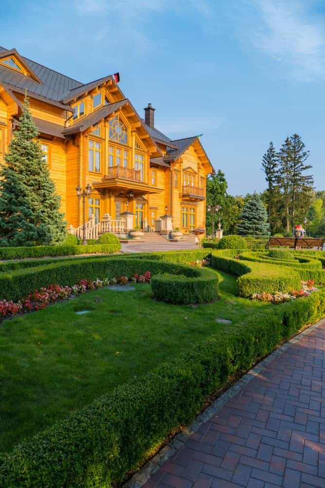 Grand wood mansion with upper wood balconies overlooking manicured grounds that include hedges and flower gardens.