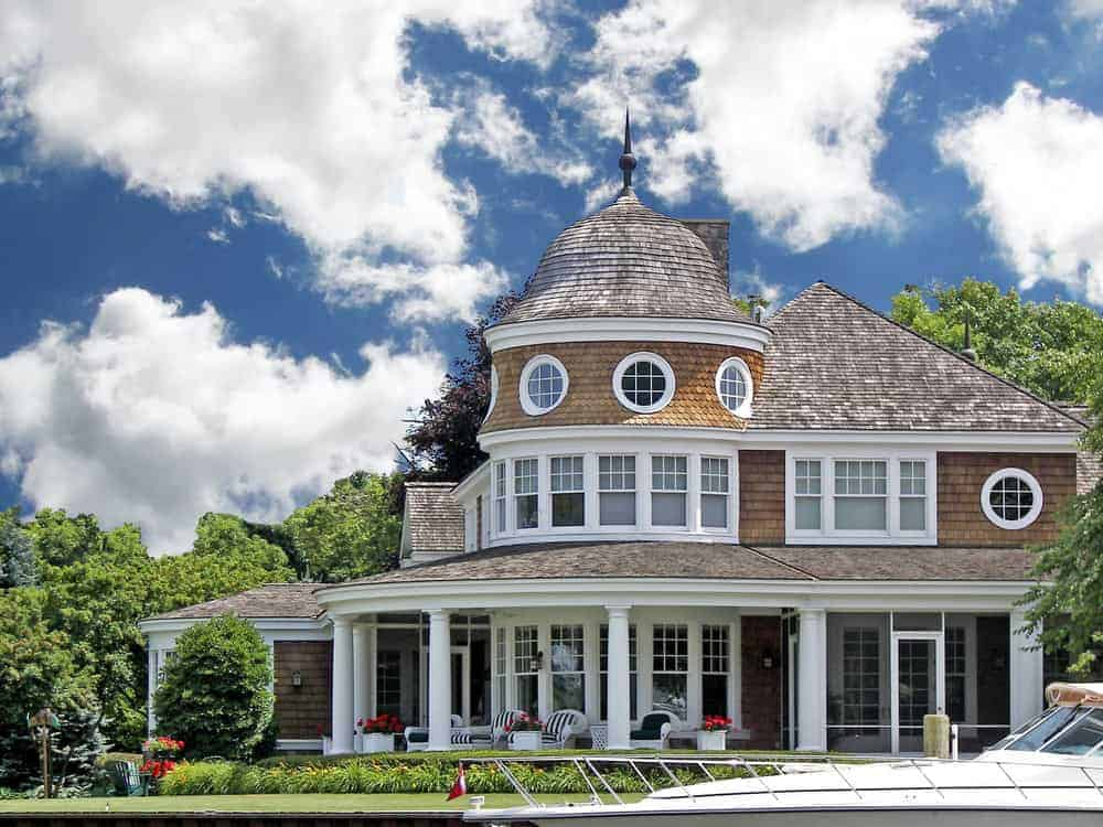 Ocean front wood shingle exterior mansion with round tower and plenty of white trim. This is without a doubt a stunning home built with plenty of nautical features such as the round, dome tower and round windows.