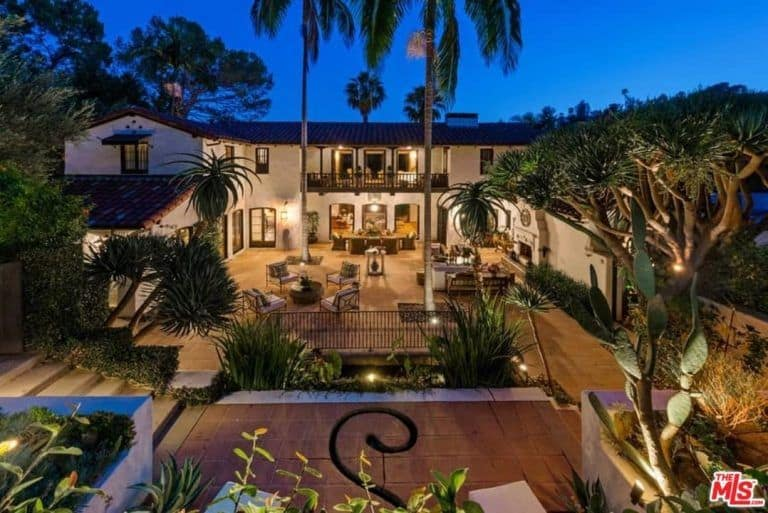 The outdoor aerial view of the property during night time captures its beautiful landscaping and lighting.