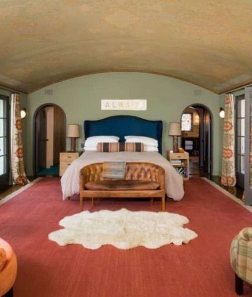 The master suite features a huge bed on a red rug along with a couple of classy seats. There's a doorway leading to the private balcony and outdoor amenities.
