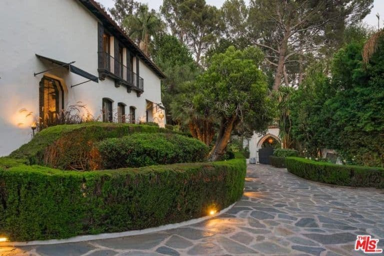 The courtyard is surrounded by well-placed plants and trees lighted by multiple warm lights.