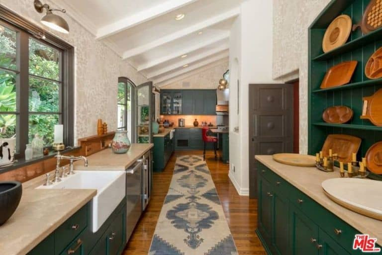 The home features a long kitchen with marble countertops and top-of-the-line appliances along with green cabinets and shelves.