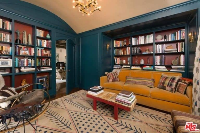 There's also a reading room in the house featuring a mustard color couch with a small coffee table on top of the rug along with elegant lighting and multiple book shelves.