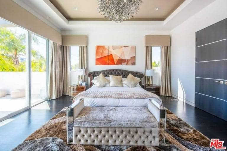 Fabulous primary bedroom boasts a tufted leather bed with a mirrored bench on its end lighted by a fancy chandelier. It has full height glass windows and dark hardwood flooring topped by a lovely brown rug.