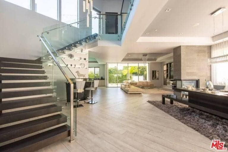 The home's entry leads to elegant indoor featuring living spaces and staircase.