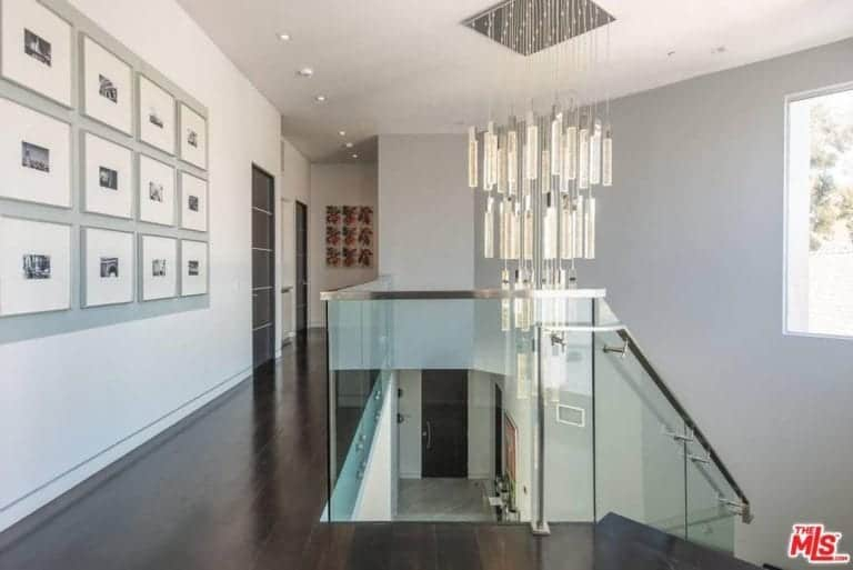 The staircase leads to the hallway featuring hardwood flooring and white walls along with glass staircase railing and elegant chandelier lighting.