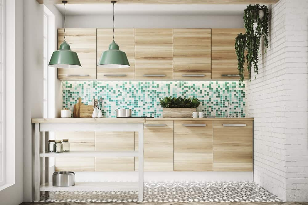 Modern kitchen with light wooden flat cabinetry, green and white tile mosaic backsplash, white brick walls and tile flooring.