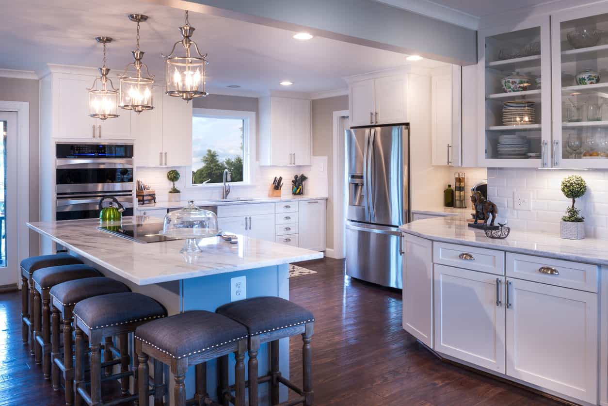 Transitional kitchen with ornamental lantern-like pendant lights, backless studded island stools (6 of them) and white cabinetry throughout. I love the chrome <a class=