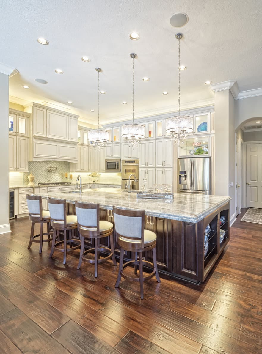 It doesn't get much finer than this U-shape kitchen design with chandeliers above the 4 person island, custom white cabinetry, crown molding and reddish dark flooring. While it's an ornate kitchen, it's also one that's comfy to congegrate in. My one criticism is that there are no windows.