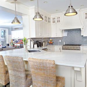 White kitchen with chrome pendant lights, blue backsplash, dark hardwood flooring and wicker breakfast bar stools.