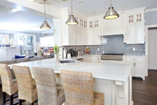 White kitchen with chrome pendant lights, blue backsplash, dark hardwood flooring and wicker breakfast bar stools.
