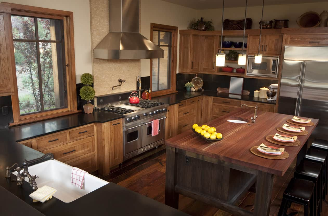 You just have to love that wood-topped custom island with small sink on one side and breakfast bar on the other side. The wood framed windows that flank the chef's stove and range are a nice touch as well. This is a true farmhouse style kitchen.