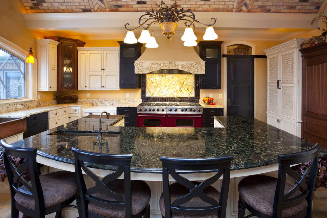 This is a large eclectic Mediterranean style kitchen with huge U-shaped island. I love the layout, but otherwise there's way too much going one with dark, white, yellow and red colors as well as an overly ornate stove hood as well as ornate chandelier capped with faux brick ceiling.