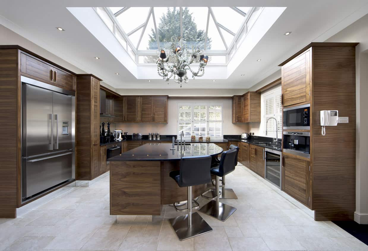 Huge walnut cabinet and island kitchen with a spectacular large skylight ceiling. This is one of those kitchens that grabs your attention, especially with that skylight ceiling. I'm not fond of the off-white tile flooring though. It looks to old fashioned for the walnet cabinetry and otherwise contemporary design. The chandelier above the island is far too ornate as well.