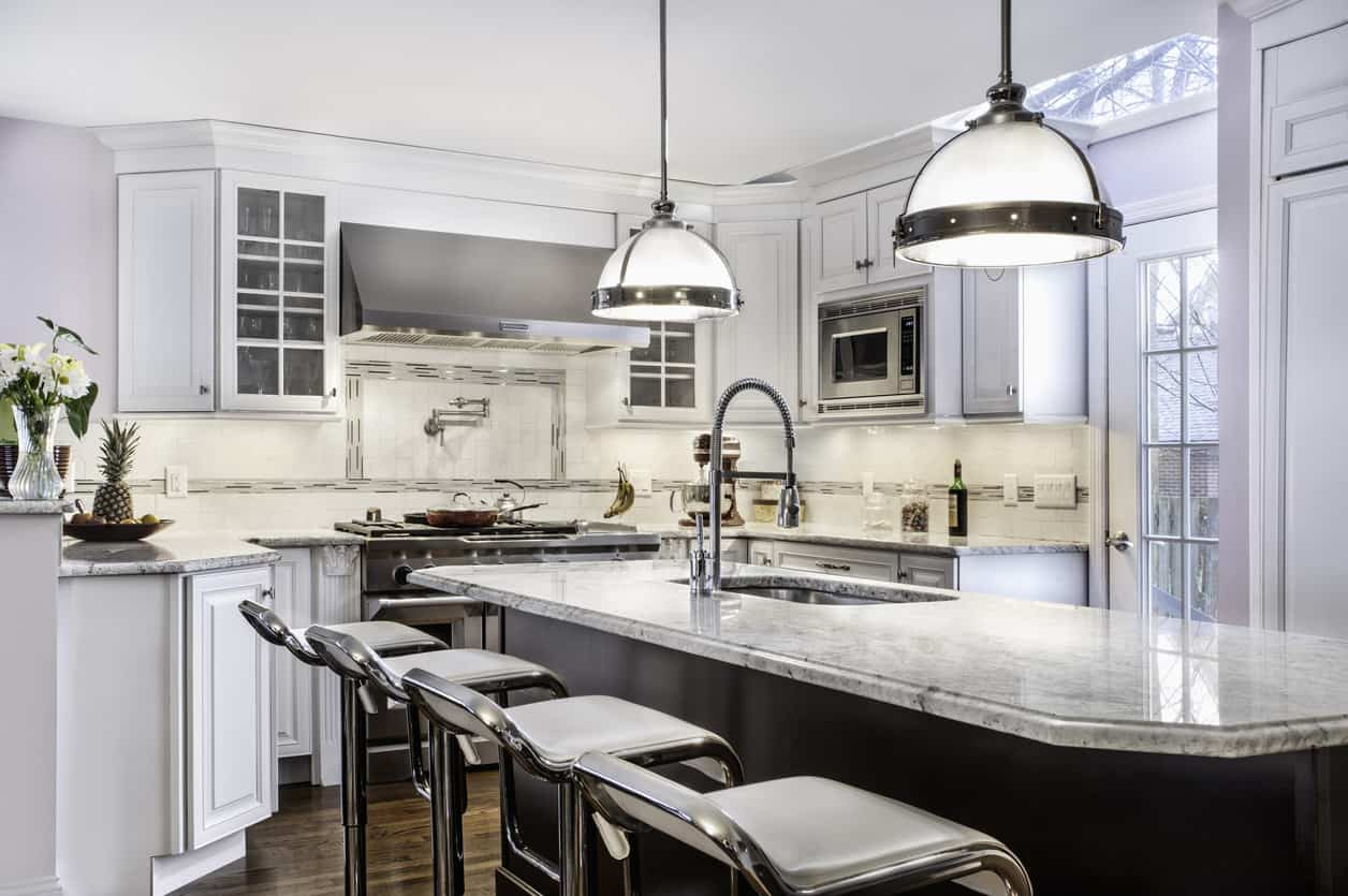 Modern meets ornate. Notice the chrome modern stools and contemporary pendant lights that juxtapose the ornate cabinetry. It's a nice mix that works spectacularly well in this overall white kitchen with dark island base. The ceiling is a bit blah, but it's not catastrophic by any stretch of the imagination.