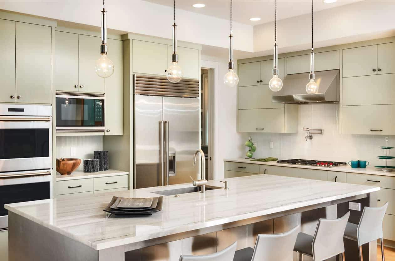Contemporary bright muted green and soft beige kitchen with bulb pendant lights, contemporary cabinetry and stainless steel appliances. This kitchen is well lit with 5 pendant lights and many recessed lights.
