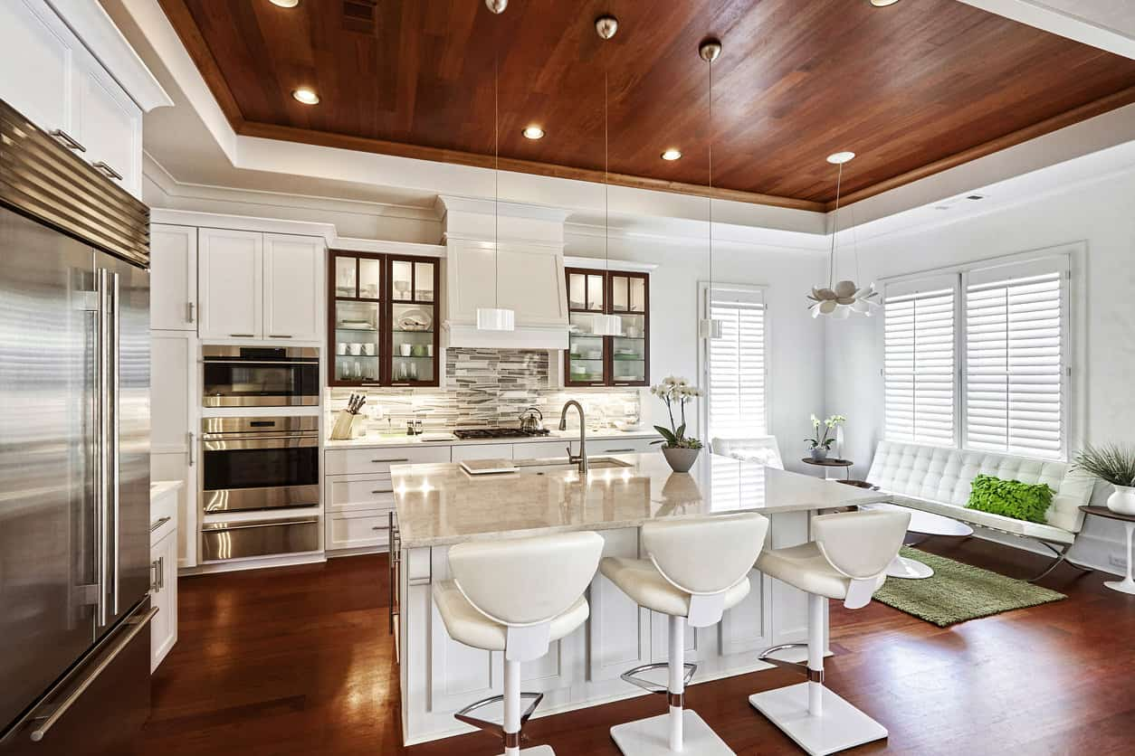 Stunning. I love the red wood floor and ceiling in contrast with the otherwise all white kitchen. That ceiling is particularly cool. The cabinetry and backsplash as well as expensive breakfast bar stools are all amazing. A lot of thought went into this kitchen design. It's a bit funky, but not overly soo. I also like the small family area adjacent to the kitchen creating a comfortable in-kitchen lounging space.