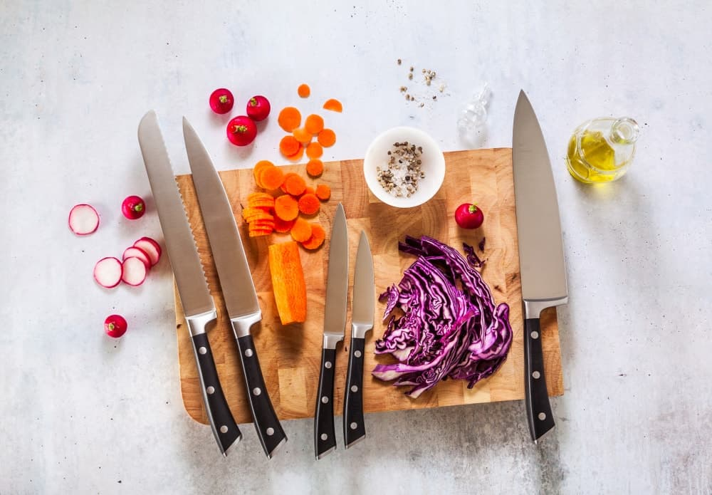A set of new professional kitchen knives on a wooden cutting board and vegetables.