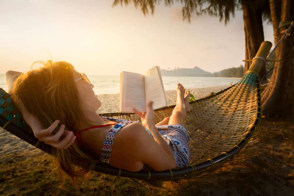 A lady lying on a hammock whilre reading a book and waiting for the sunset.