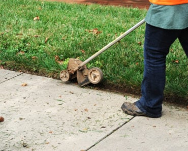 A man using a lawn edger to maintain his lawn and enhance the landscape of his garden.