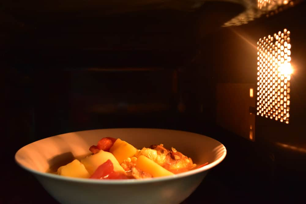 A bowl of food being heated inside the microwave oven.