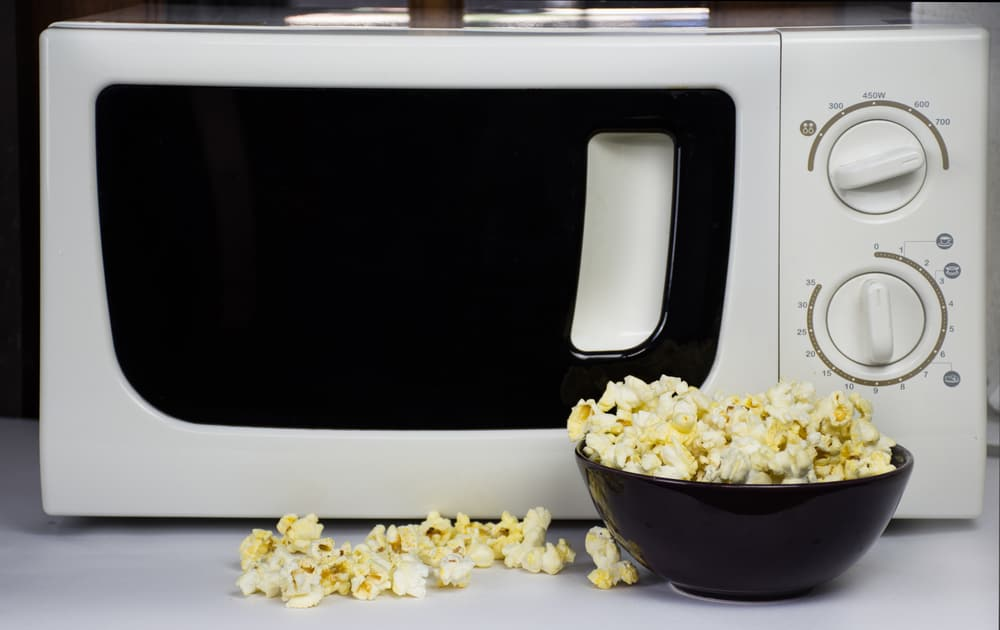 A small bowl of soft popcorn and a white microwave oven.