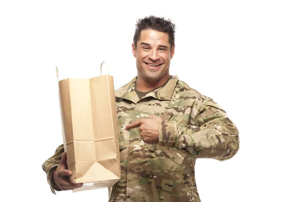 Military man carrying a grocery bag.