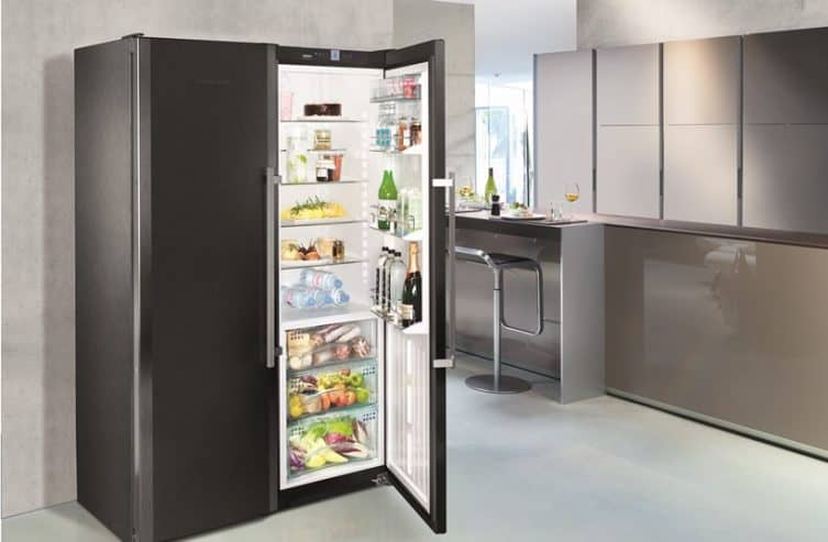 A modern two-door refrigerator with a lot of stuff inside.