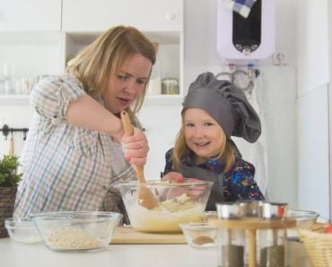 A mother and daughter using plenty of mixing bowls for baking.