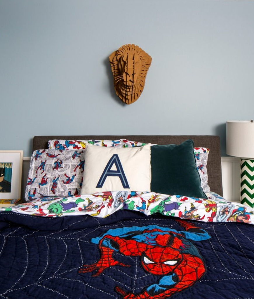 The home also has a bedroom for boys boasting a plain blue walls with a wall decor. Photo credit: Sean Litchfield