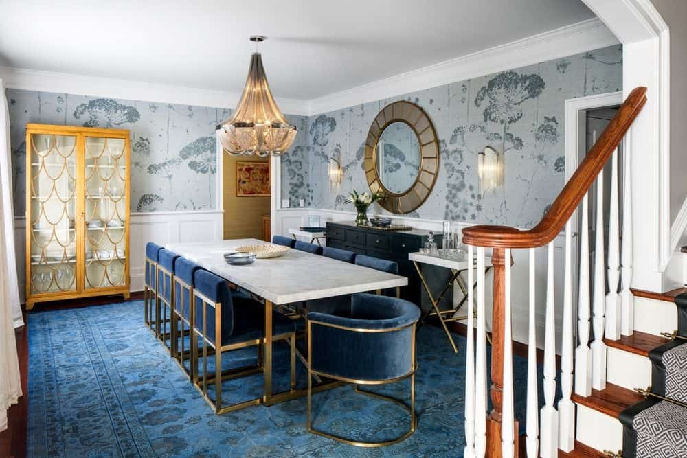 Elegant dining room decorated with a round mirror and a spectacular chandelier that hung over the marble top table surrounded by sleek velvet chairs. Floral wallpaper and a blue area rug bring an inviting and welcoming vibe in the area.