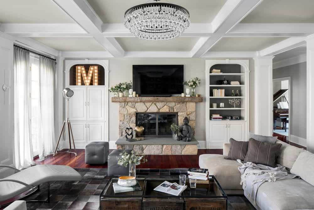 A fancy round chandelier that hung from the coffered ceiling illuminates this living room offering a television and stone fireplace in between white storage cabinet and built-in shelving.