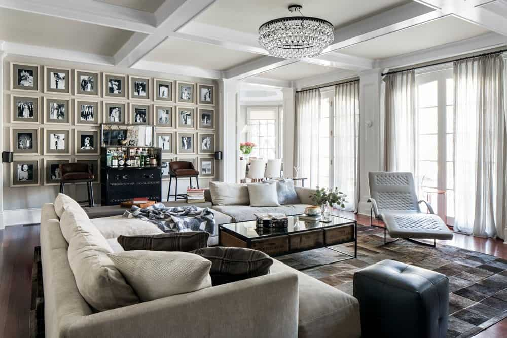 Large living room with interesting wall design and ceiling lighted by a gorgeous ceiling light. The seats are set beautifully on a stylish rug.
