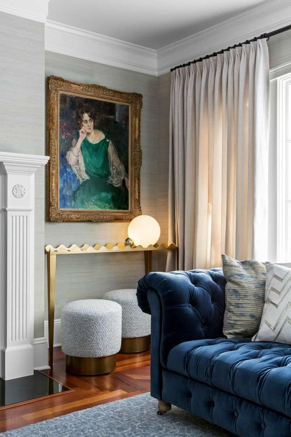 Close up look of the living room's beautiful sofa, flooring, rug and a classy portrait wall decor. Photo credit: Sean Litchfield