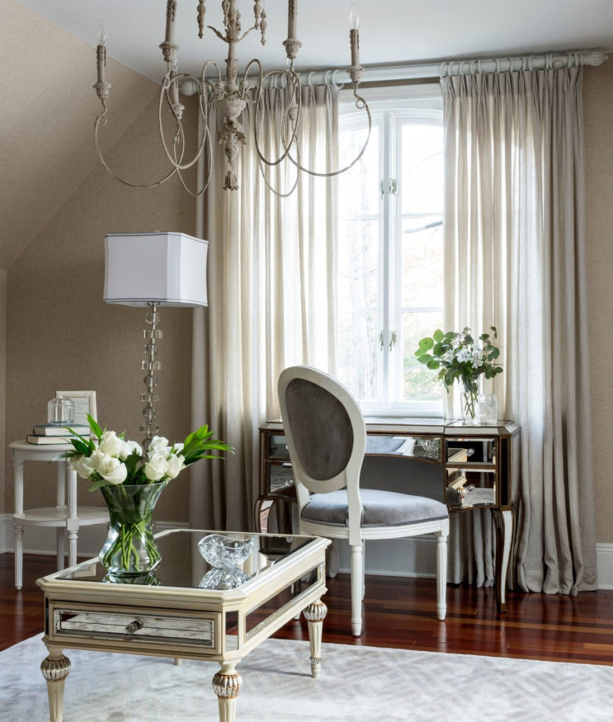 The bedroom also has a console table and a elegant chair lighted by chandelier and lamp. Photo credit: Sean Litchfield