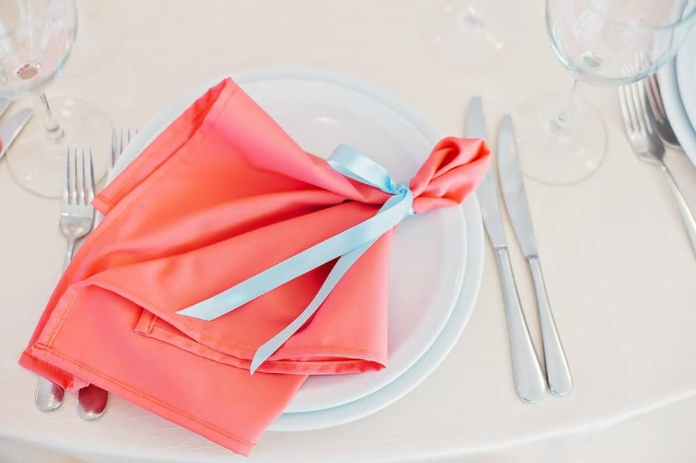 Table napkin tied with a blue ribbon placed on a table setting.