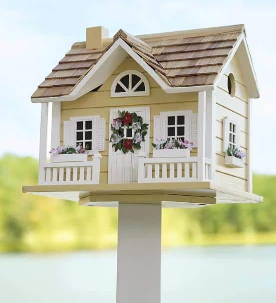 A post-mounted birdhouse looking like a real house.