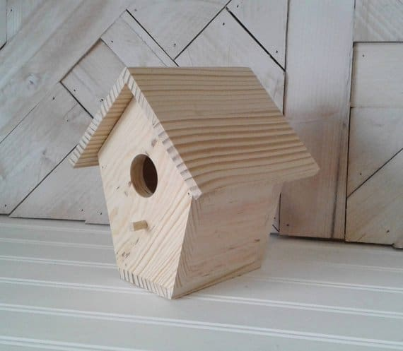 Small, wooden birdhouse with a natural tone.