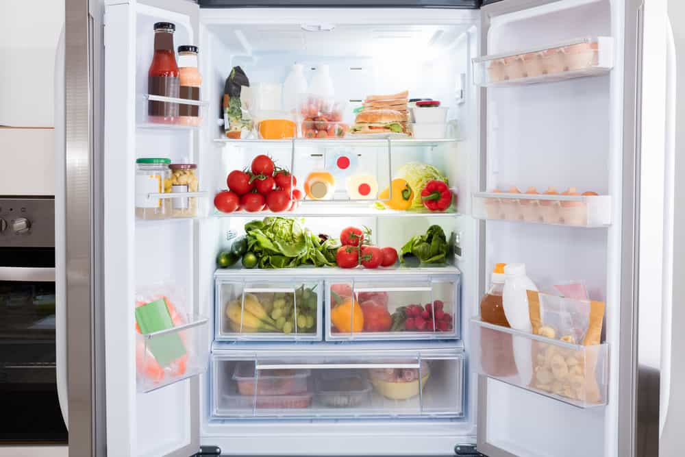 Open refrigerator filled with fresh fruits and vegetables.