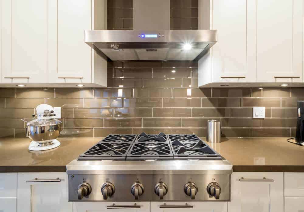 Cooktop with an overhead hood.