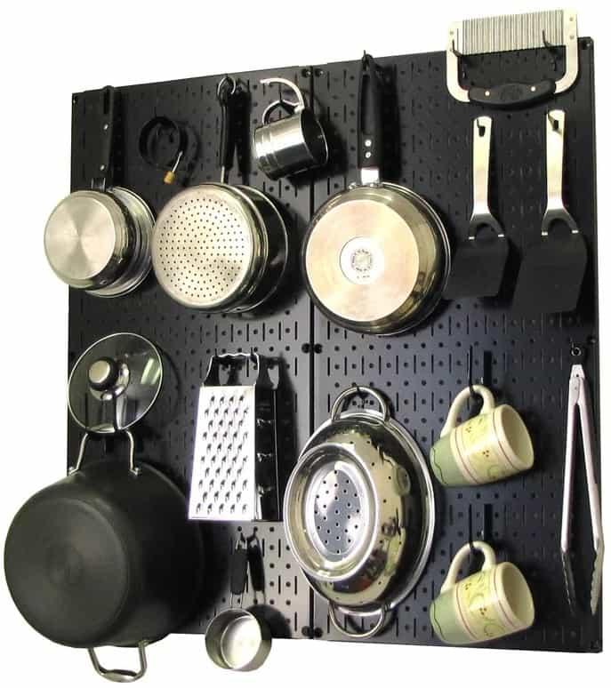 Kitchen cookwares on a black, metal pegboard pot rack.
