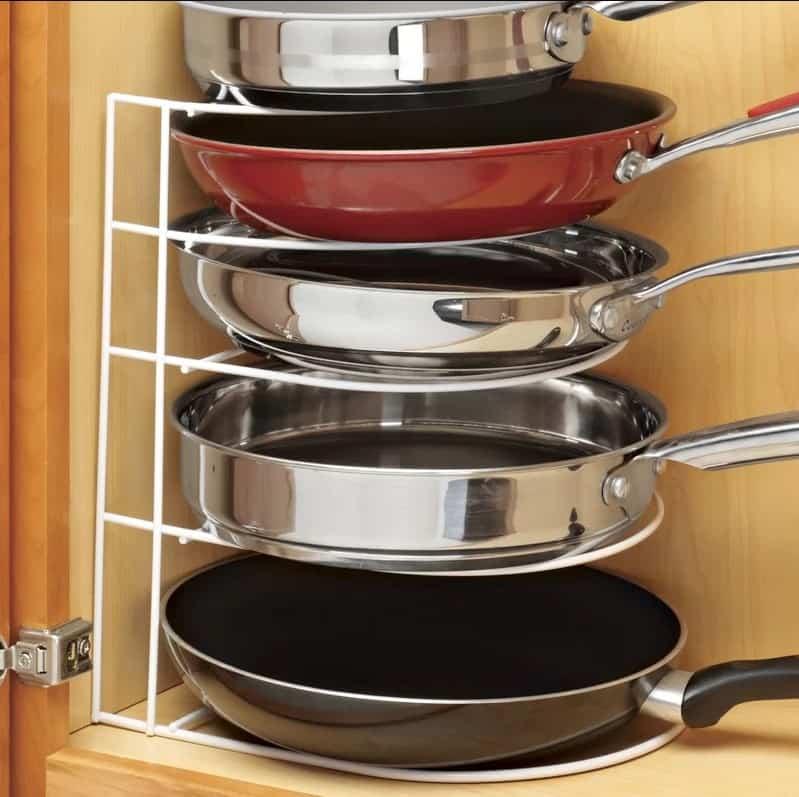 Frying pans organized on a white plastic pot rack.