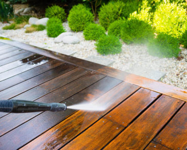 Using pressure washer on dirty, wooden floors.