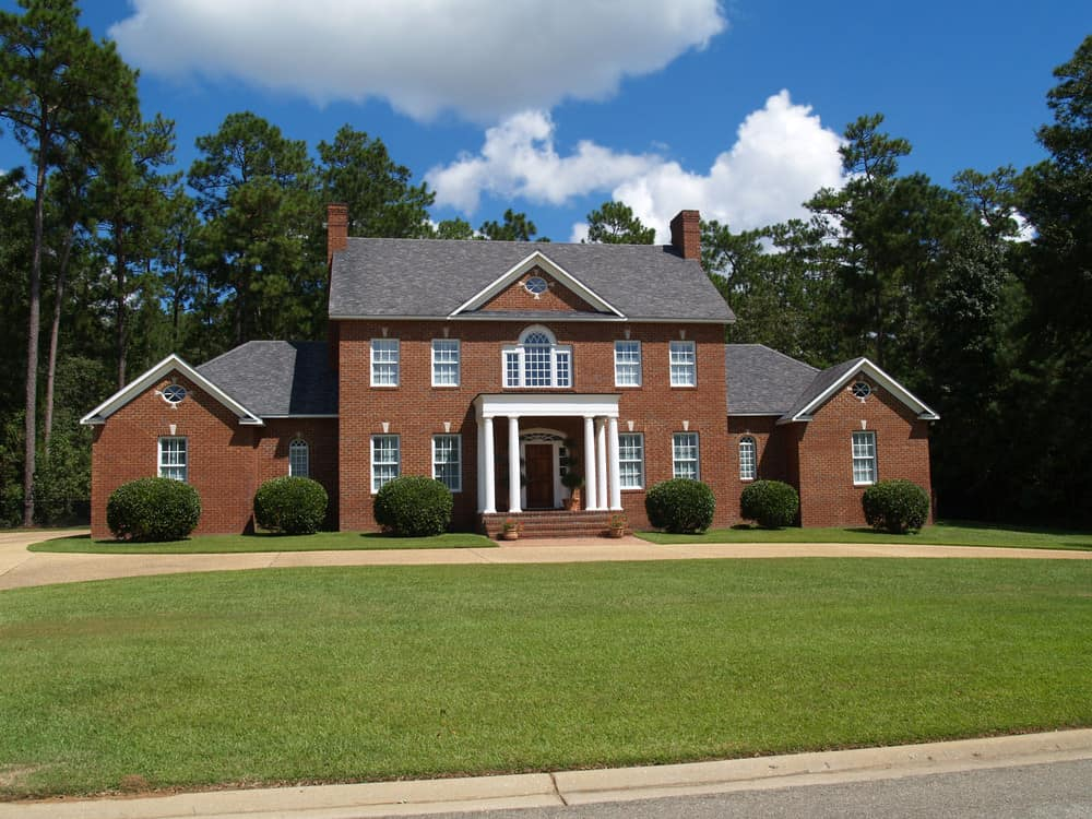 Large country home with single story white columns at the front door for covered front entrance. Brick chimneys on each side of the home.