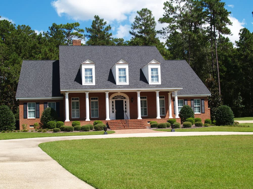 Quaint two story brick home with 6 columns capped with three dormers set against dark grey shingle roof.