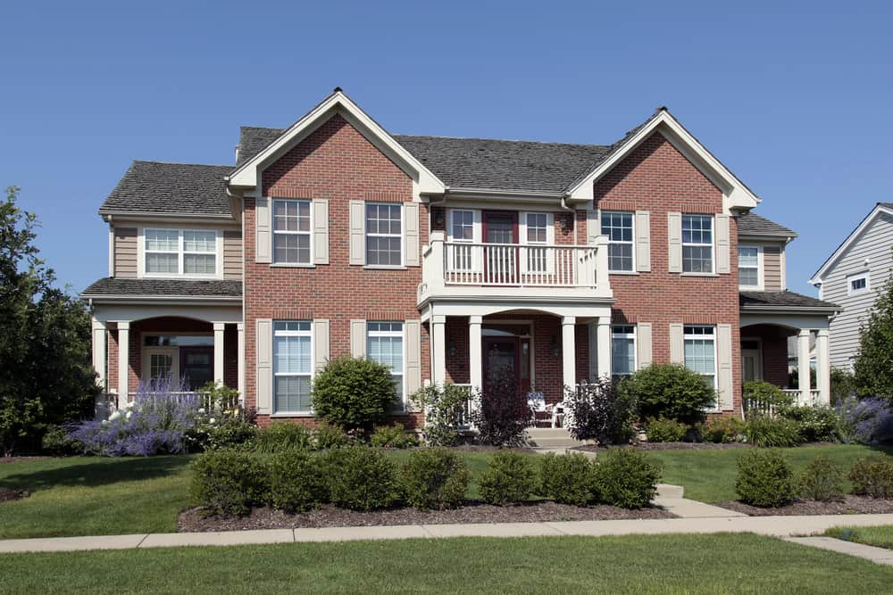 Elegant upscale suburban home with red brick and beige exterior shutters.