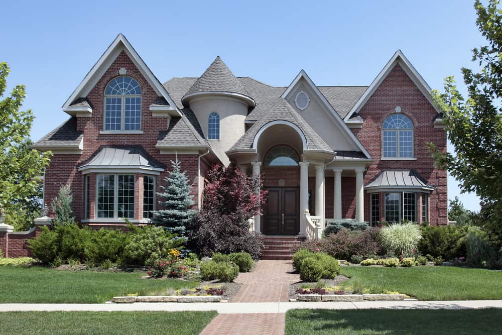 Fancy home with turret, column, bay windows, steeply peaked roof lines in suburb.