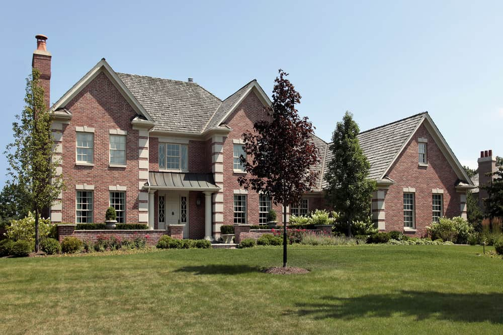 Large brick home in upscale neighborhood. Tall brick chimney on one side of the home.
